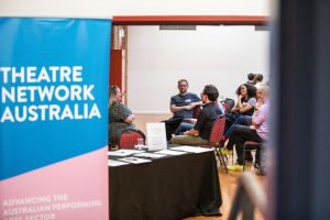The left half of the image shows the blue, pink and white Theatre Network Australia banner. The right half of the image shows a semi-circle of 5 independent producers, seated.